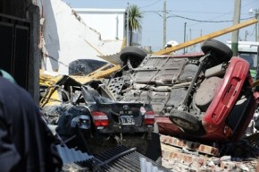 Two wrecked cars appear next to houses d